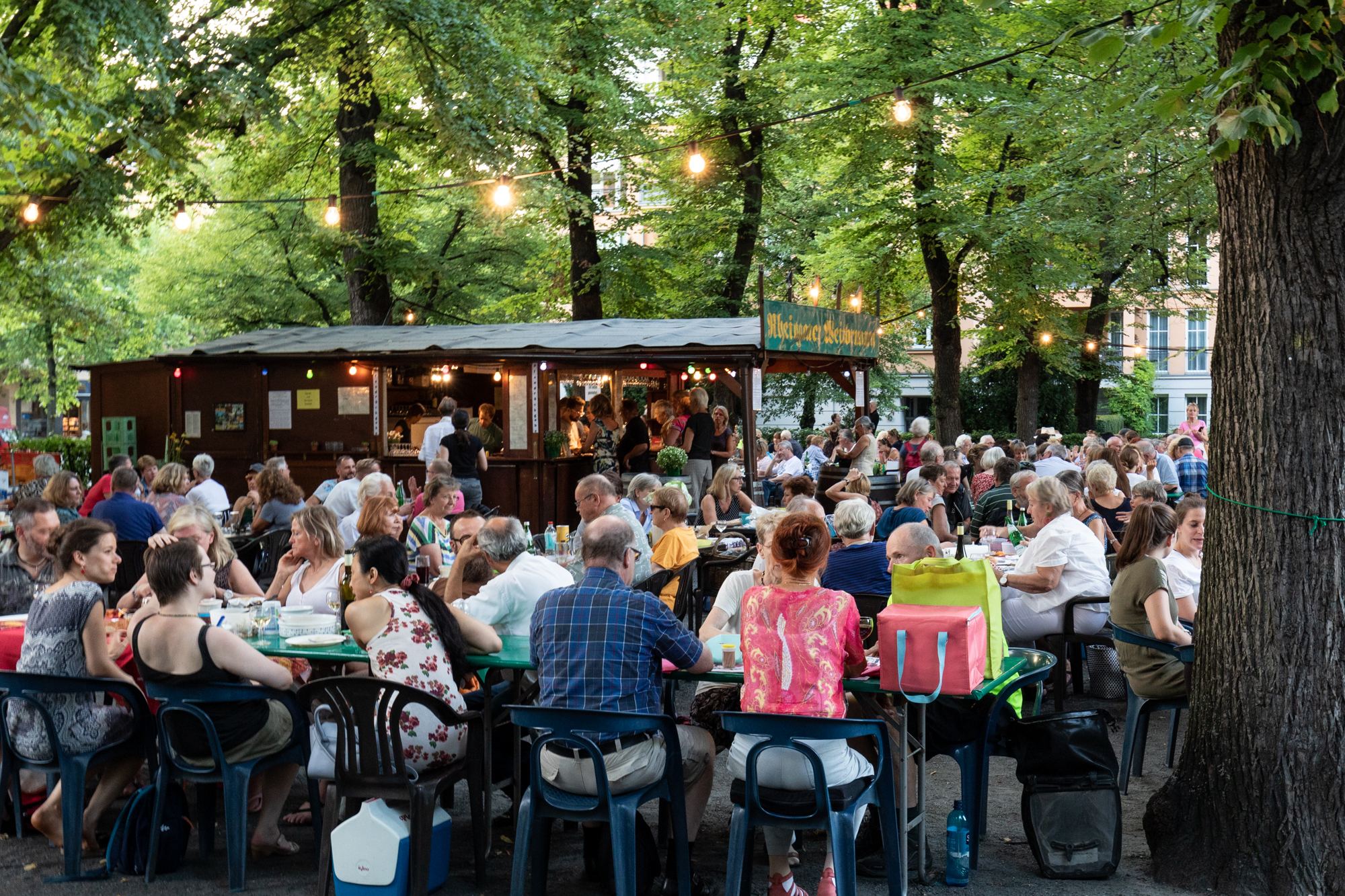 Guests enjoying picnics and wine at Rheingauer Weinbrunnen - a wooden hut serving wines from Rheingau-Taunus district of Hesse on the Rüdesheimer Platz in Berlin Wilmersdorf
