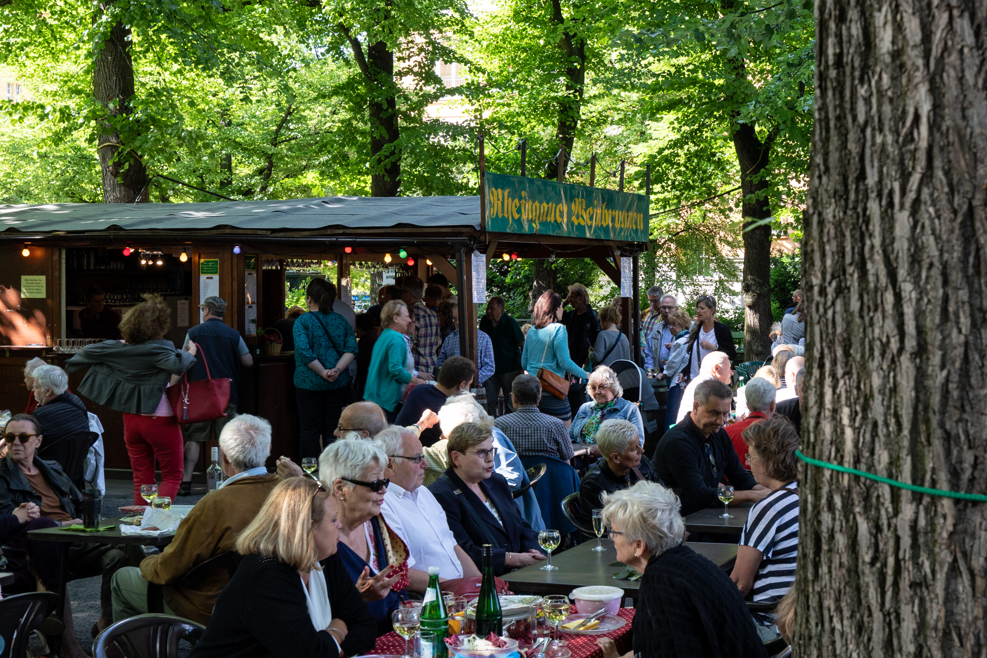Guests under the trees at Rheingauer Weinbrunnen - a wooden hut serving wines from Rheingau-Taunus district of Hesse on the Rüdesheimer Platz in Berlin Wilmersdorf